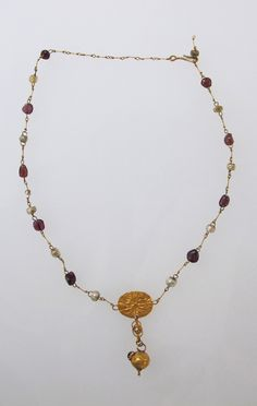Necklace with pendant and glass beads Date: 1st century B.C.–2nd century A.D. Culture: Roman Medium: Gold, glass paste Dimensions: Diameter: 5/8 × 1 1/16 in. (1.6 × 2.7 cm)