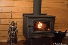 L'intérieur du Chalet le Malard.Le Poêle à bois agît aussi comme chauffage d'appoint par une froide nuit d'hiver. Statue de métal avec accessoires pour le poêle | mur en bois rond, mur en cèdre blanc, poêle à bois noir, poêle en fonte noir, porte en vitre trempée, feu, poignée de bois, tuyau de cheminé noir, seau à cendres noir, pelle à cendres noire, chevalier en armure en étain, plancher simili bois