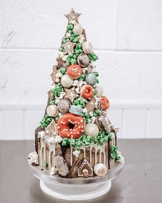 A Christmas Croquembouche with gingerbread men, houses, stars, doughnuts, macarons, profiteroles, eclairs, popcorn, chocolate bark and CAKE all the way through by Cliff