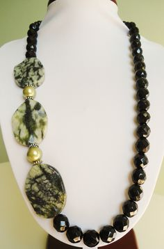 A lovely and elegant asymetrical necklace made from Jungle Jasper ovals, Sparkling black Czech fire polished presioca beads, silver spacer beads and green glass pearls.