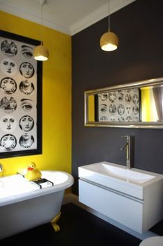 Brighten up your bathroom with yellow walls and Fornasetti art.