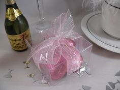 Clear square box with pink and silver ribbon, with 5 pink chocolate foiled hearts inside