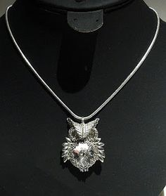 """From Carl's Beading Table: Owl Pendant / Anhaenger """"Eule""""Materials used: DB035 galvanized silver, 11/0 (Miyuki 1051) galvanized silver, Miyuki Long Magatamas (LMA 1051) galvanized silver, Miyuki 15-194 palladium plated, 15/0 Delicas palladium plated, 8 mm chatons and 18 mm rivoli crystal non AB, silver snake chain with sterling silver findings."""