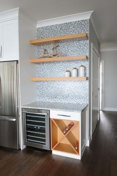 Three styled maple shelves mounted to beautiful blue mosaic tiles hover above a stainless steel, glass-front wine fridge sat next to a built in cross cut wine rack positioned under a white and blue granite countertop.