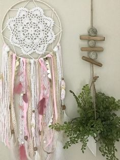 This pink and gold dream catcher will add a whimiscal bohemian touch to any bedroom or nursery. It will keep all the bad dreams away, leaving room for only the good ones! This boho dream catcher is made up of the following: - Ivory, white, gold and baby pink ribbons, lace and yarn. - Pink and white feathers - Stones and wooden beads - This dream catcher comes with three coordinating hand painted feathers with the option to add more. Measurements: 8 wide 28-30 long Please contact me for any…