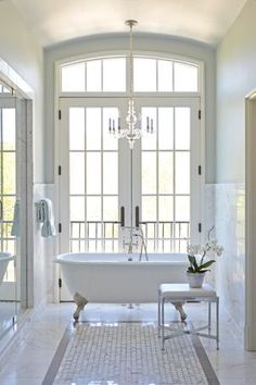 White clawfoot bath in white classic bathroom