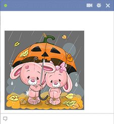 This cute pair of bunnies is hanging out in the rain under a fun jack-o-lantern umbrella.