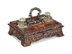 AN EARLY VICTORIAN BRONZE-MOUNTED TORTOISESHELL, MOTHER-OF-PEARL AND IVORY-INLAID INKSTAND CIRCA 1840 With two cut-glass inkwells flanking a rectangular lidded compartment with two pen rests above a frieze drawer, surmounted by an entwined dolphin handle