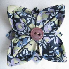 Knotted Cotton: How to make an origami Liberty fabric brooch. Surely by using bigger squares you could use the tutorial to make a pincushion.