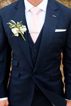 Navy suit, pink tie, pink buttonhole stitching