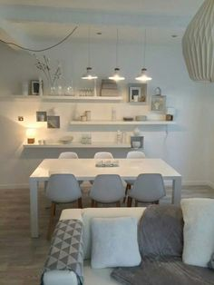 Simple white and light grey dining area with pendant lighting. The asymmetrically set shelves and decor add depth and visual interest to the room.