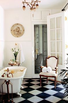 Checkered tile, tub,high ceilings, French door with 3/4 window--It all works together to create old-fashioned elegance.