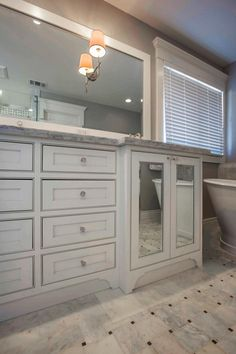 The designer bumped out the sinks to create different depths, added an arched toe kick and used beaded inset cabinets to give this vanity a furniture look. Combining the large drawers into one large cabinet and adding mirrors to the doors makes the fixture look custom built.
