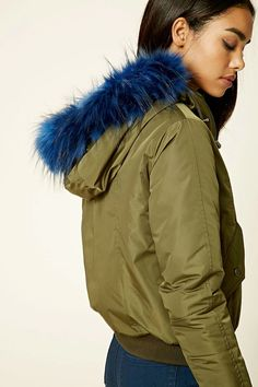 A padded bomber jacket featuring a hood with contrast faux fur trim, drawstrings, zip-up front, two front flap snap-button pockets, ribbed trim, a zippered accent, and long sleeves.