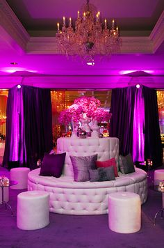 A white circular banquette and modern pods are surrounded by pink phalaenopsis orchids and small votive candles.