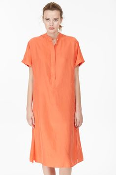 Dress made of high-quality medium-weight silk with intensive colour. Light washed effect due to a garment-dyed finish. Half concealed button border at front. Shoulder yoke. Short sleeves with turned hems. Insert along side seam. Double piped pocket in insert. Long side slits. Pearl buttons.