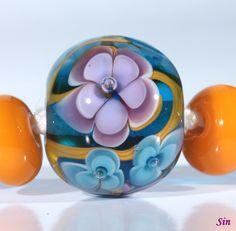 Handmade glass lampwork bead with flower pattern. (21 x 17 mm).