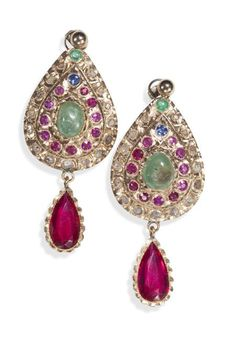 A pair of Indian gold mounted multi-gem set ear pendants, each of ovoid form, set throughout with cabochon cut emeralds, circular cut rubies and synthetic rubies, sapphires and diamond macles, suspending a large pear cut synthetic ruby drop, with detachable ball surmounted post and disc fittings. Provenance: Lord Curzon of Kedelston, Viceroy of India, via his daughter Lady Cynthia Curzon.