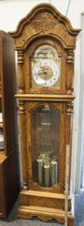 BEAUTIFUL SLIGH GRANDFATHER CLOCK IN A LIGHT OAK WOOD, IN WORKING CONDITION. STANDS 7 FT. TALL X 22 W. X 12 IN. D.