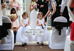"""Flower Girls - front of sign says """"here comes the bride"""" and when they walk back down the aisle the other side says""""...And they lived Happily Ever After."""""""