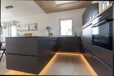 Dunkle und moderne Küche im HARTL HAUS Kundenhaus. Helle Holzdetails stechen in dieser Küche hervor. Corner Desk, Kitchen, Table, Furniture, Home Decor, Houses, Hip Roof, Kitchen Contemporary, Timber Wood