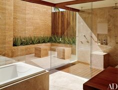 Sliding glass doors link an ipe-floored master bath to a secluded patio featuring aloe vera plantings and travertine cubes | archdigest.com