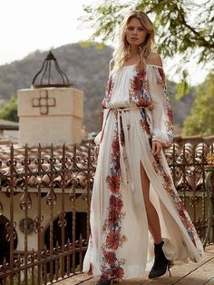 Bardot Printed Maxi   Floral printed off-the-shoulder maxi dress with a sweeping silhouette and blouson top. Effortless fit with long sleeves featuring elastic cuffs. Cinched waist with tie accent. Lined with a silky slip.