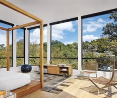 Expansive windows and a sharp, teak canopy bed with modest furnishings make this second-story master bedroom a minimalist, modern treehouse-like sanctuary.