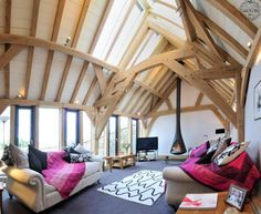 Barn interior by Carpenter Oak. Check out the cool woodburning stove that actually hangs in space.