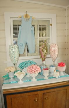 Vintage baby shower candy station...1940's children's jumper hangs on a shabby chic window pane.  The candy is presented in antique Milk Glass.  Cynthia Ferris-Bennett 775.671.2164 or Cynthia@SierraChef.com