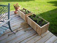 terrasse en bois avec deux bacs à fleurs en lattes de bois clair