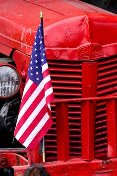 Digital photograph of an old red tractor with an American flag taped to its fender with duct tape created on location