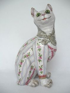 A Continental Faience cat, in the manner of Galle, wearing a jacket painted with bands of roses interspersed with pale blue bands, with green glass eyes, and painted with a headscarf, unmarked, 33cm (damaged). I like the 'stripes' on this cat.