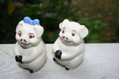 Cute Pig Salt and Pepper Shaker Set. White with black hands and feet. She has a blue bow in her hair. Their tails are shaped like S (him) and P