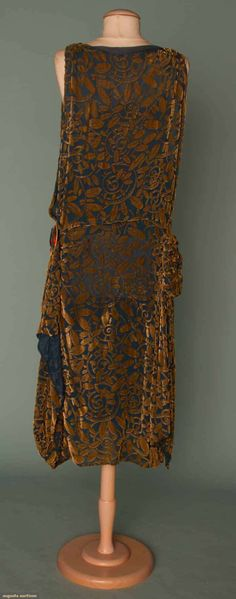 CUT VELVET PARTY DRESS, c. 1923  Deco pattern taupe velvet cut to marine blue chiffon, 2 side panels, 1 w/ self fabric rosette & 1 w/ large celluloid disc w/ metal figure of Japanese woman, bodice sides are open to show marine blue underdress