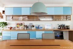 Sala de jantar de casa de vila tem mesa de madeira e buffet com portas em tons de azul.