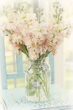 Stock flowers in mason jar - This is what I am planning on doing with the mason jars exactly. Using light pink stock flowers.