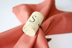 Great Idea, a wine cork napkin ring. She just used ribbon through a hole in the corks. What else could you use?.....