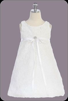 If you want a slightly less formal look for her Communion this is the perfect dress. This beautiful white dress knee length dress features embroidered fabric flowers, an empire waist with a ribbon sash and a rhinestone brooch.