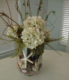 Teresa on Blissfully Domestic posted this beautiful beachy summer arrangement. I think when I first saw it, I sighed. I love beach decor! Find: One clear vase An assortment of sea shells Five hydrangea stems Curly willow stems Two stems. Beach Cottage Style, Beach House Decor, Beach Flowers, Wedding Flowers, Wedding Stuff, Wedding Ideas, Hortensien Arrangements, Shell Decorations, Wedding Decorations