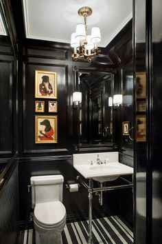 Take risks in the smallest room. The powder room or small downstairs bathroom is a space where you can indulge the most adventurous decorating ideas, such as this gentlemen's-club look with black lacquered paneling and playful artwork. Traditional Powder Room by Ofer Wolberger, LTD.