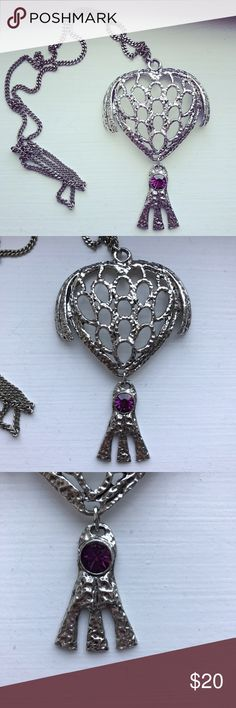 Pullover silver hamsa evil eye necklace Pullover silver tone hand-hammered hamsa (hand of God) necklace with an evil eye purple gemstone, made to look like an amethyst, in the center. This is a different take on the tradition religious-style hamsa, with the upper hand almost resembling a heart and the evil eye and three central fingers hanging on a pendant. The hamsa measures 3.75 inches by 2.25 inches, and is lightweight. The chain is linked, and has a drop length of 13 inches. This is in…