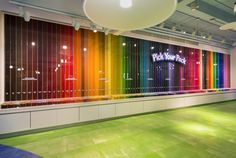 Crayola Experience -  The 40-foot Pick Your Pack wall is a rainbow display of 75 different colored crayons and 24 markers striping 11 feet to the ceiling. At the foot are bins of individual crayons and markers for shoppers to create their individualized boxes.