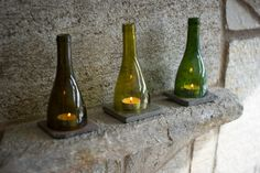 Upcycled glass bottles creatively fashioned into decorative tea light holders rest on the original fireplace mantle.