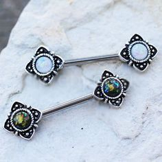 • 316L Stainless Steel Nipple Bar with flower design and synthetic opal • Partially Black plated for a Medieval look • Rope design around synthetic opal for extra flare • Elegant flower shaped design