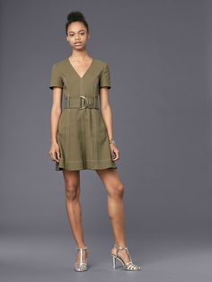 This short-sleeved dress features a detached belt with a D-ring closure that creates a subtly feminine silhouette. Finished with light top stitching and two oversized pockets at the waist, it features a two-way, gold tone, exposed zip down the center-front.