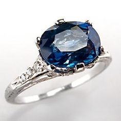 This early 1900's antique blue sapphire engagement ring features a high quality cushion cut center stone and gorgeous old European and single cut diamond accent stones. This certified ring is crafted of solid platinum and features intricate filigree and mill grain details.