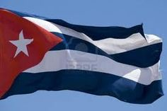 ''The Cuban flag '' was created by Narcisco Lopez and sewn by Emilia Teurbe Tolon in 1847. The blue stripes represents the sea that surrounds the island.  The white stripes symbolize the purity of Cuban cause, and the red triangle stands for the blood shed to free the nation. The white star in the triangle stands for independence. Tres listas azules, dos listas blancas, un triángulo rojo y una estrella de plata.  Así es la bandera de Cuba, mi patria.