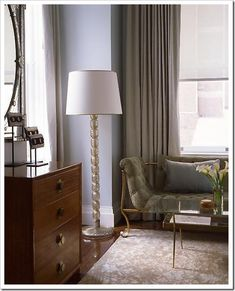 I prefer this combination of grays, because it looks more intentional. A more sophisticated analogous colour scheme with the blue gray walls and toss cushion paired with the greeny gray drapery, upholstery and carpeting.