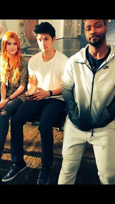 Katherine McNamara (Clary Fray), and Harry Shum Jr. (Magnus), and Isaiah Mustafa (Luke)